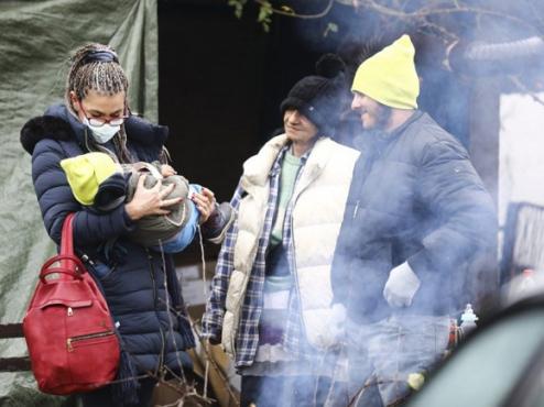 Fotografija obitelji s malom bebom ispred u potresu oštećene kuće