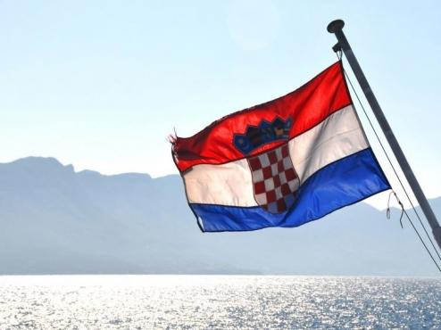 Fotografija hrvatske zastave koja vijori iznad mora